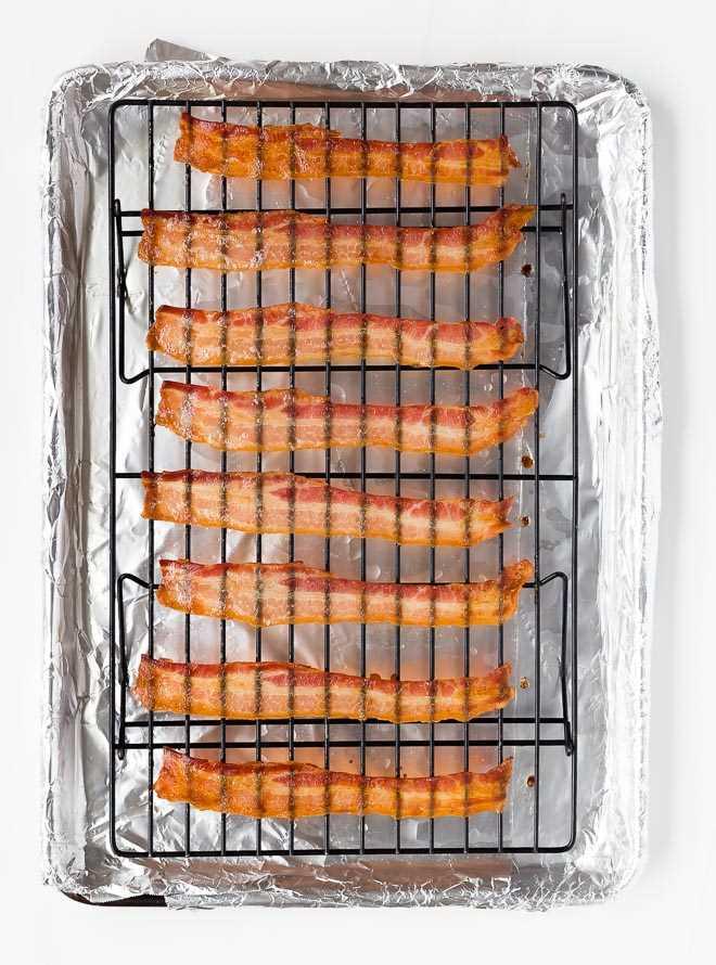 Imagen de tocino cocido crujiente sobre una rejilla para hornear en una bandeja para hornear.