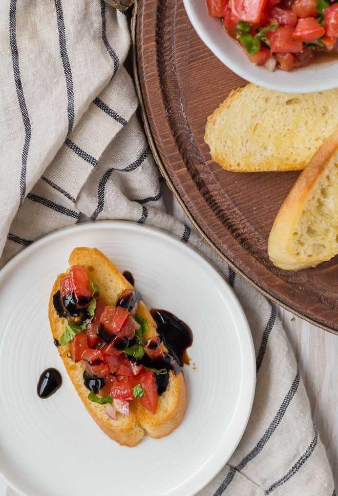 Fotografía de bruschetta clásica de tomate con albahaca y glaseado balsámico.