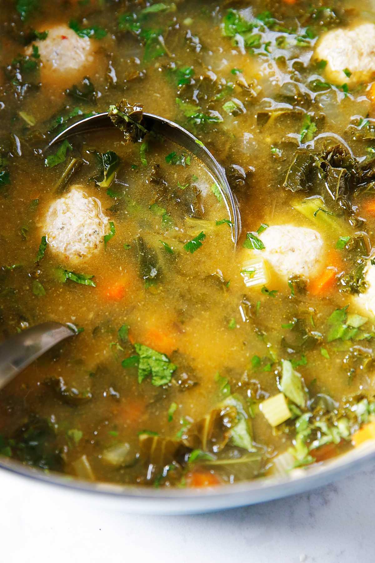 Una olla de sopa de boda italiana con col rizada.