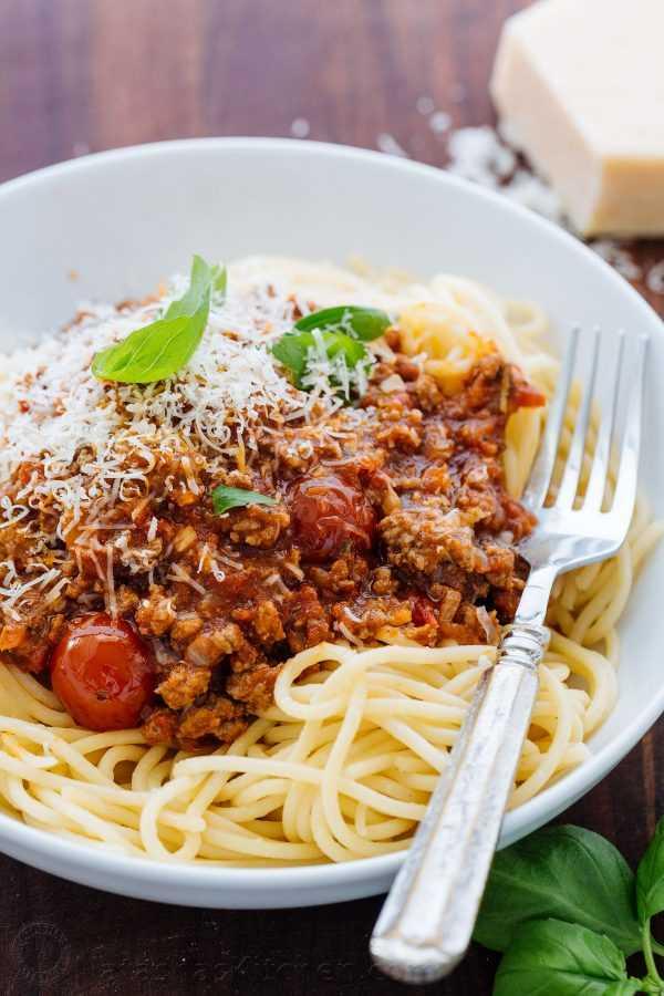 Salsa de carne de espagueti en un tazón de espagueti con queso parmesano y albahaca