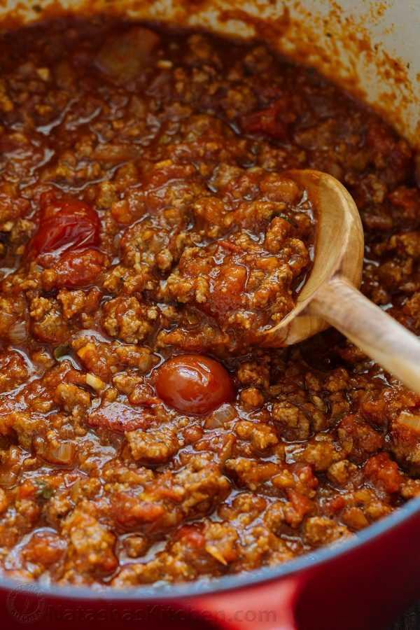 Salsa de carne descongelada recalentada en una olla con una cuchara mezcladora