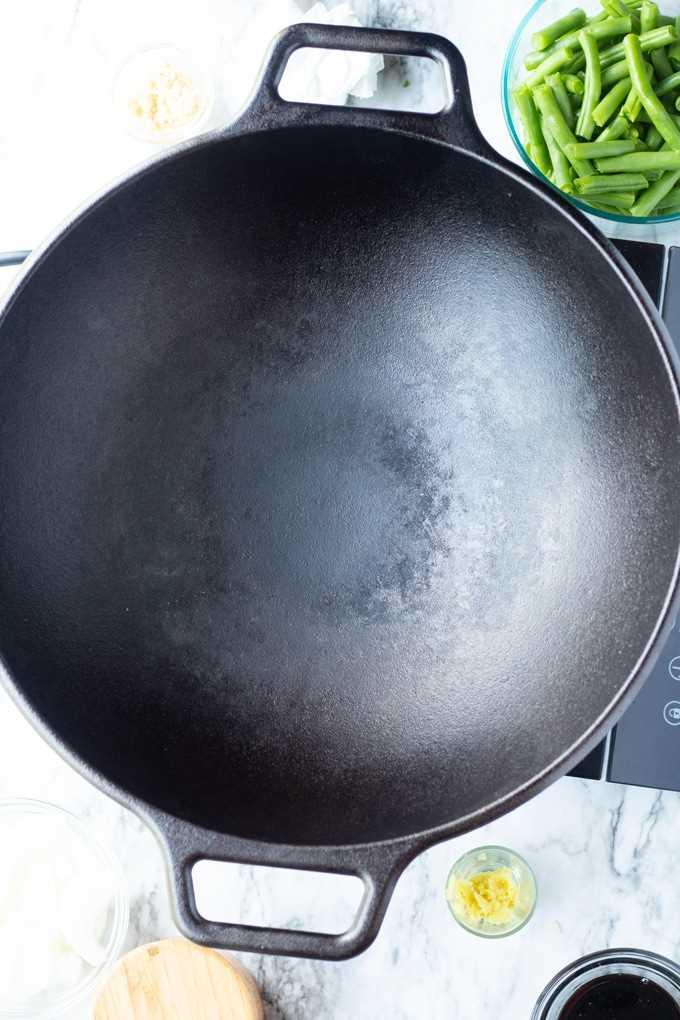 wok de hierro fundido con judías verdes en el costado