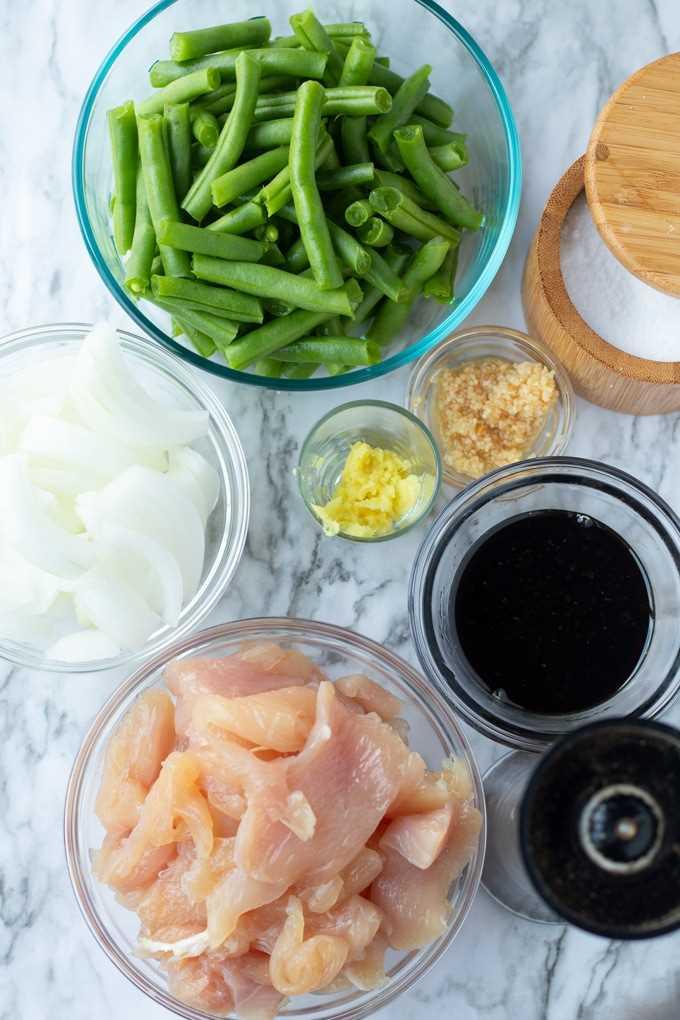 judías verdes, sal, ajo, giner, cebolla, salsa y pollo en tazones pequeños