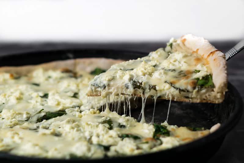 levantando uma fatia de queijo de cabra e pizza de espinafre