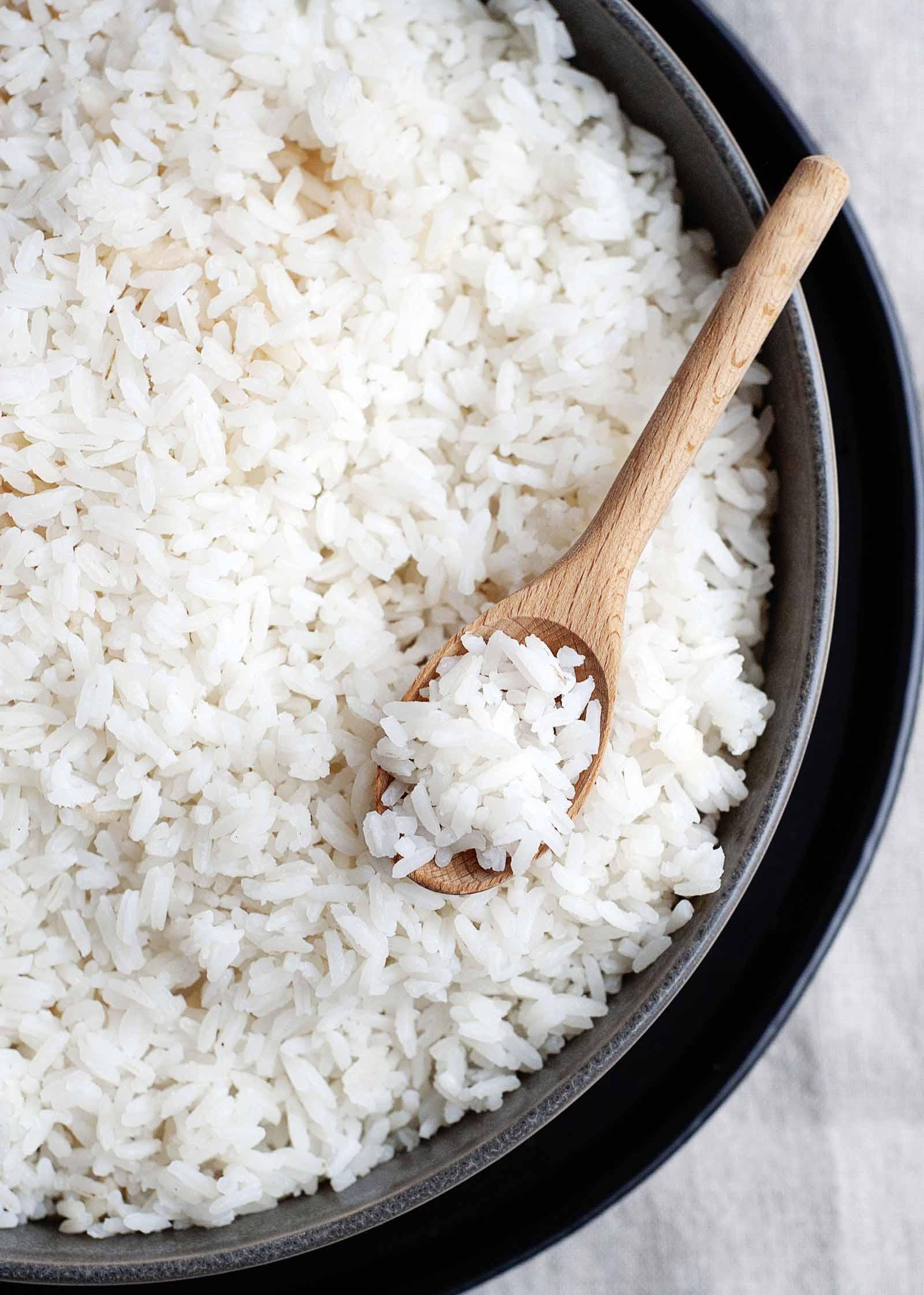 Arroz blanco fácil en una sartén de metal sentado en una bandeja profunda con una cuchara de madera llena de arroz dentro.