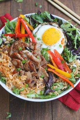 A bowl full of mixed vegetables, pork bulgogi, bell peppers, fried egg, and kimchi fried rice.