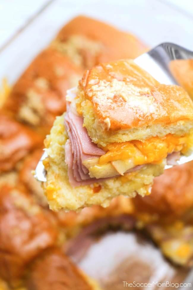 Una combinación irresistible de sabroso y dulce: estos deslizadores de mantequilla, jamón al horno, manzana y queso cheddar son la receta perfecta para la fiesta de fútbol de otoño.