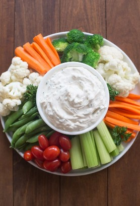 Uma bandeja circular cheia de legumes (tomate, cenoura, brócolis, couve-flor, aipo, ervilha) com um fácil molho de vegetais no centro.