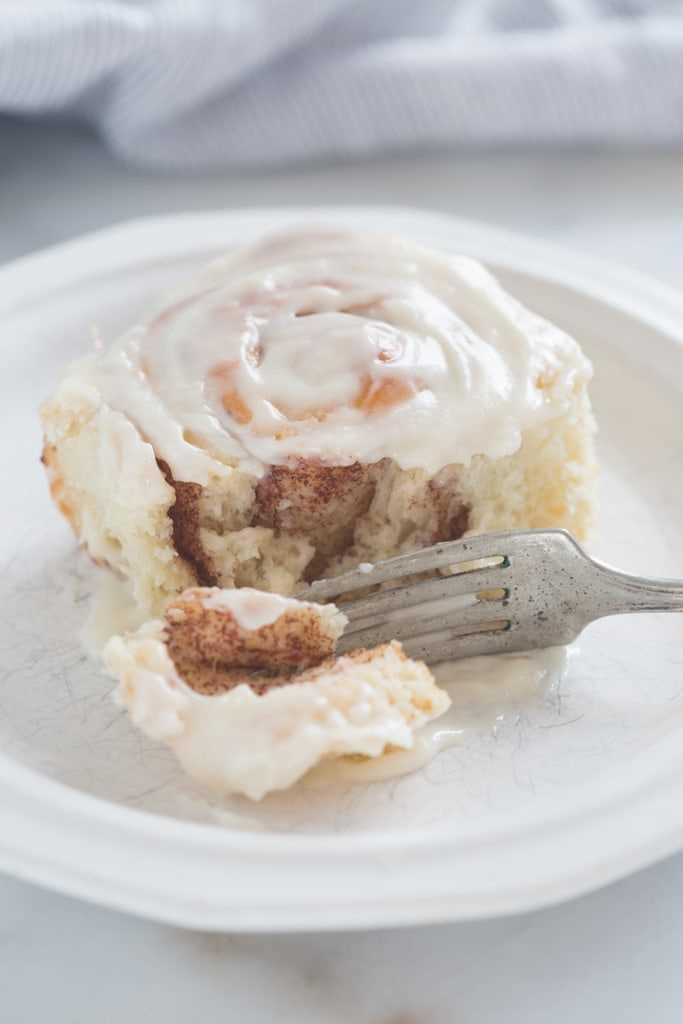 Un rollo de canela en un plato blanco con un tenedor cortando un trozo.