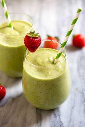 Smoothie verde em dois copos com um canudo e morango na borda dos copos.
