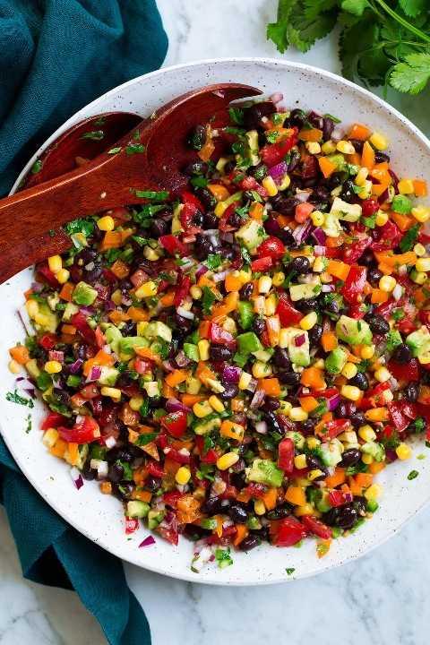 Ensalada de frijoles negros y maíz con aderezo de pimiento, aguacate, tomate y lima cilantro.