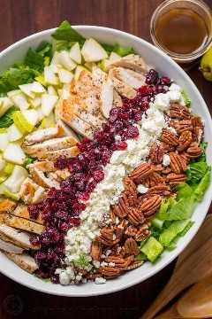 Salada de frango picada Servida em tiras de frango, peras, passas, queijo feta e nozes em uma cama ou alface com vinagrete balsâmico ao lado