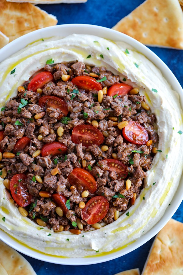 Un tazón blanco de hummus libanés con carne condimentada con cortes de pita a su alrededor en un mostrador azul.