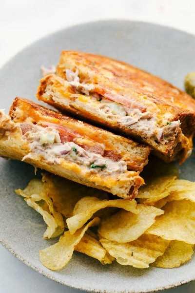 Sándwich de atún derretido sentado en el plato para que veas las capas fundidas juntas con un lado de papas fritas.