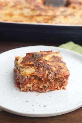 Una rebanada cuadrada de lasaña italiana en un plato blanco con el resto de la lasaña en una cazuela en el fondo.