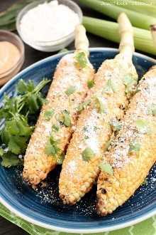 Este maíz mexicano en la mazorca se asa a la parrilla y se unta con mayonesa de chile y lima. ¡Termine con una pizca de queso y no querrá maíz en la mazorca de ninguna otra manera!