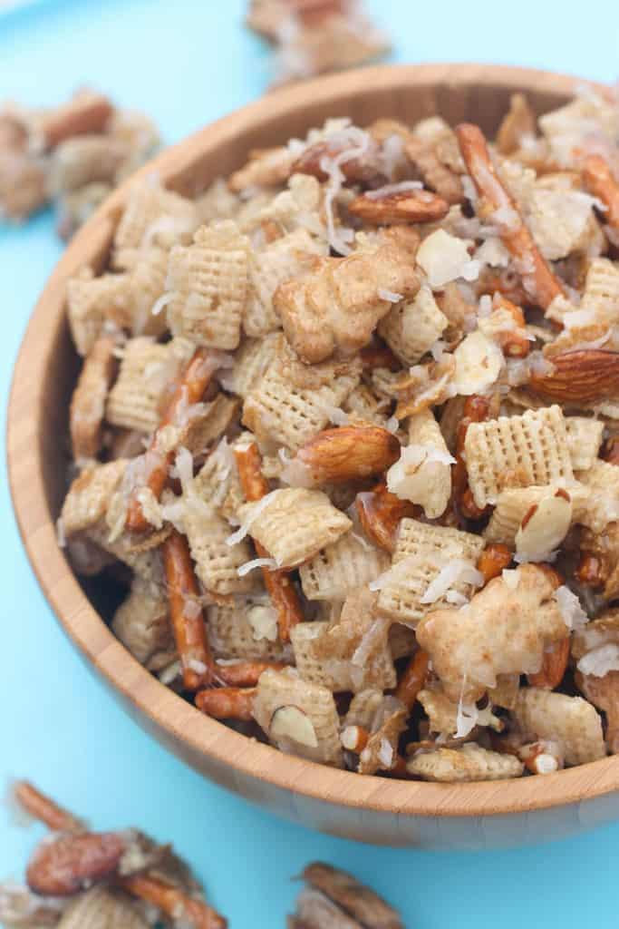 Un tazón de madera lleno de cereal Chex, Teddy grahams, palitos de pretzel, almendras y coco y cubierto con una mezcla de jarabe de maíz para hacer una mezcla de snack masticable.