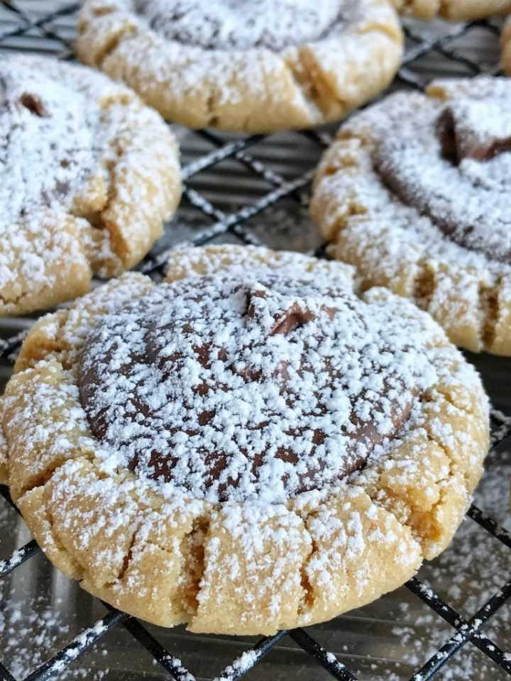 Muddy Buddy Galletas de mantequilla de maní | ¡Tu bocadillo favorito convertido en galleta! Las galletas de mantequilla de maní Muddy buddy son una galleta de mantequilla de maní suave y gruesa con un centro de chocolate y espolvoreada con azúcar en polvo. Postre perfecto o incluso mejor para un plato de galletas de Navidad. ¡Estos pueden parecer difíciles pero son realmente muy simples! www.togetherasfamily.com #christmascookies #peanutbuttercookies #peanutbutterrecipes #recipe
