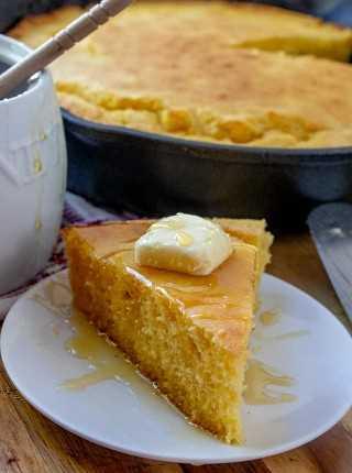Rebanada de pan de maíz en un plato con un poco de mantequilla y rociado con miel, pan de maíz en una sartén de hierro fundido en el fondo