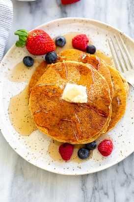 Três panquecas de trigo integral em um prato manchado com frutas e calda por cima.