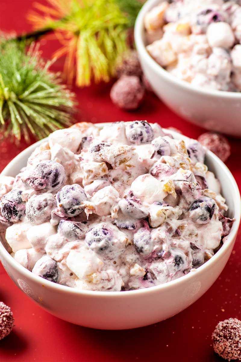Cranberry Fluff! Esta ensalada de pelusa de arándano es un acompañamiento o postre de clima frío que combina arándanos agrios, piña dulce y manzanas frescas con crema suave y nueces. El | HomemadeHooplah.com