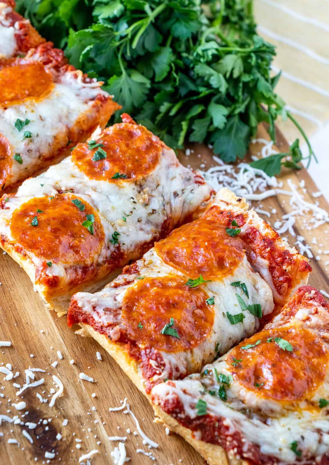 Rebanadas de pizza de pan francés en tabla de cortar con queso rallado y perejil