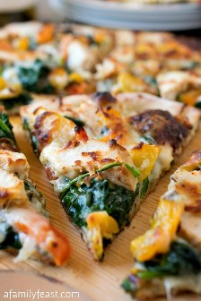 Swap your family pizza night with this delicious white chicken pizza! Grilled chicken, creamy white bechamel, pesto, peppers, spinach and mozzarella. Pizza heaven!