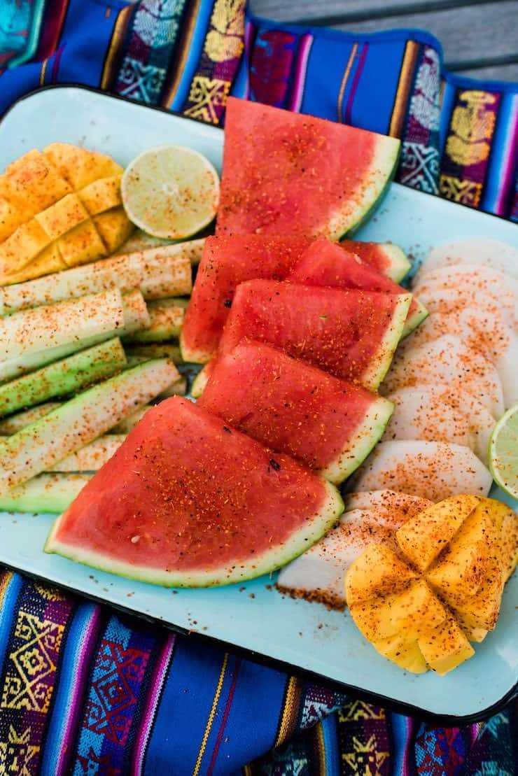 arreglo de plato de mango, pepino, sandía y jícama con chile en polvo