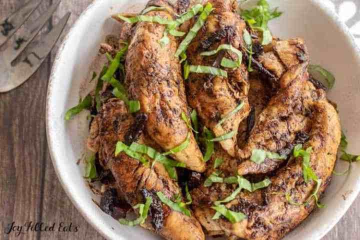un plato de pollo balsámico cubierto con albahaca fresca