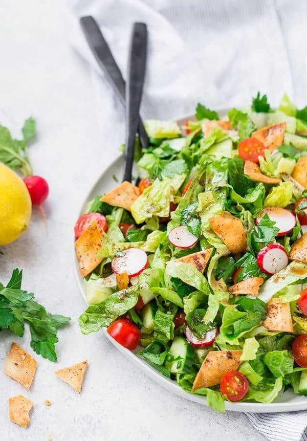 Imagem de Fattoush salada no prato com utensílios de servir preto. Decorado com salsa, hortelã, rabanete e limão.