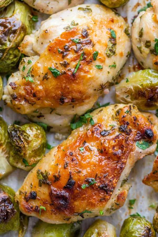 Muslos de pollo al horno en una sartén con una sabrosa marinada de ajo, limón y dijon con coles de Bruselas bañadas en el jugo de la sartén para una receta fácil de sartén con pollo y coles de Bruselas.