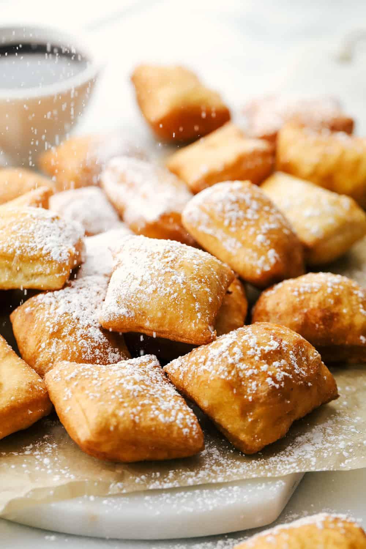 Beignets en una tabla de cortar con azúcar en polvo sobre la parte superior y jarabe de chocolate en el lateral.