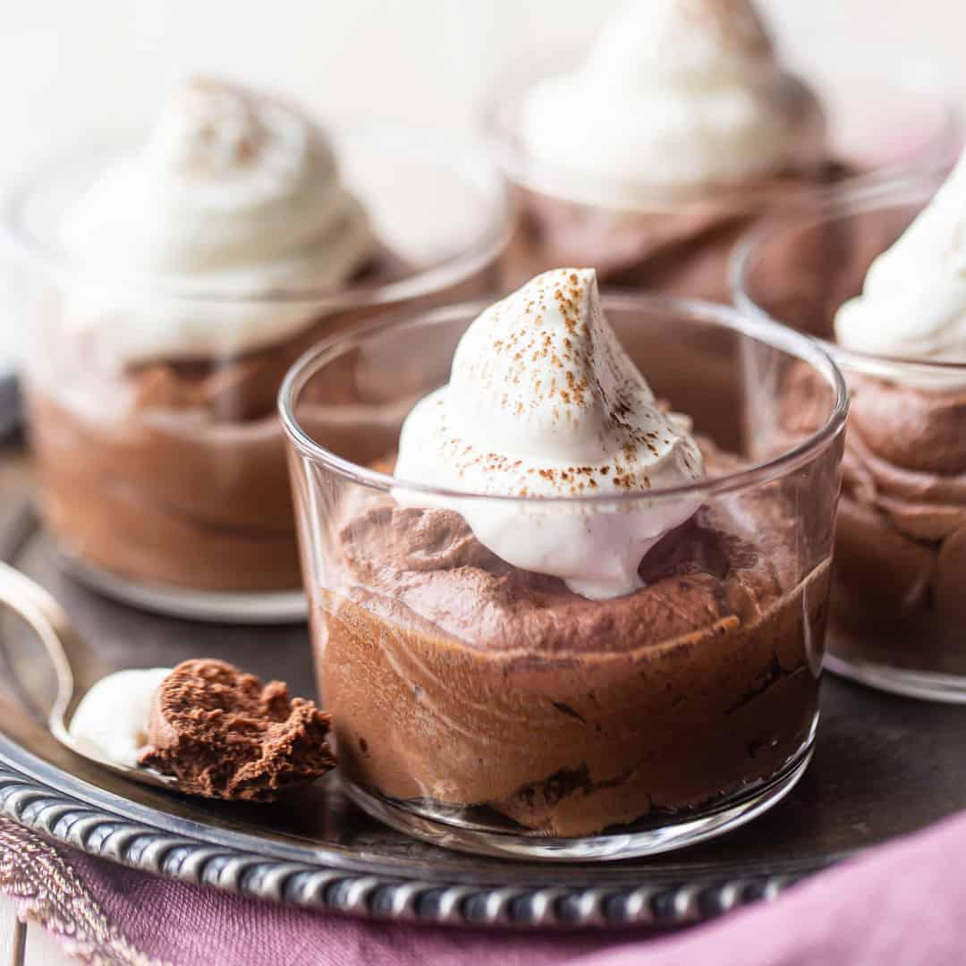 Pequeños tazones de vidrio de mousse de chocolate con crema batida en una bandeja de plata antigua.