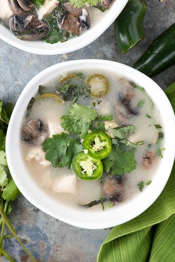Foto de cerca de un tazón de sopa de coco con champiñones de pollo tailandés
