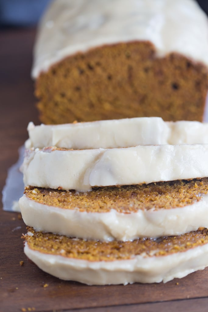 Several slices of pumpkin bread on a cutting board and topped with brown maple butter frosting.