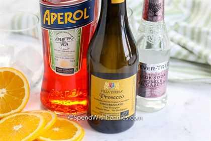 Aperol Spritz ingredientes con rodajas de naranja en el lateral.