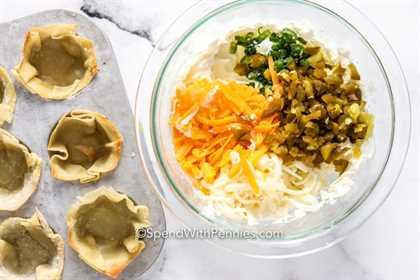 Jalapeño popper ingredientes en un recipiente de vidrio con tazas de wonton en una tapa de muffins.