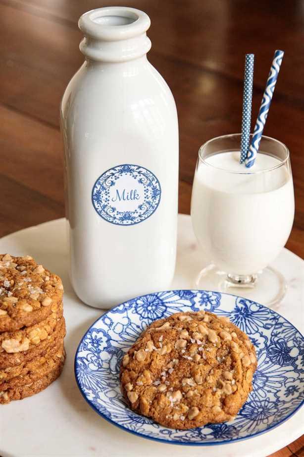 Foto de galletas de mantequilla de maní con avena y caramelo en una bandeja de mármol blanco con una jarra y un vaso de leche en el fondo.