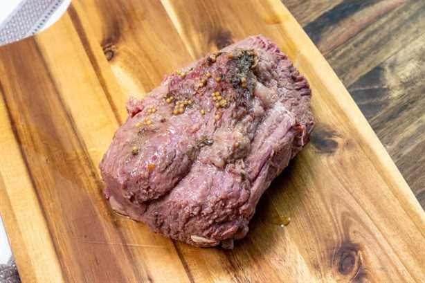 carne en conserva totalmente cocida descansando sobre una tabla de cortar