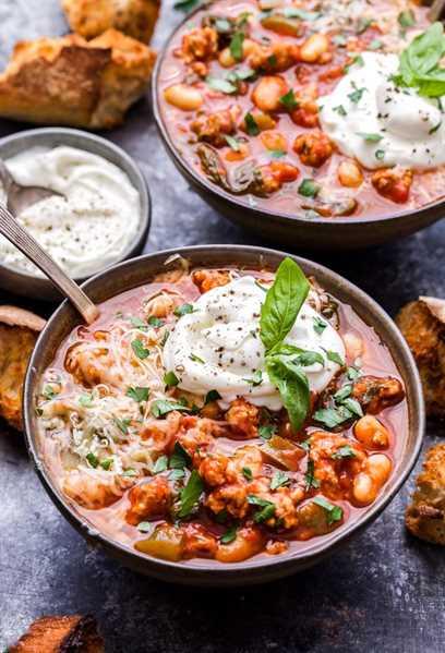 Olla de cocción lenta Italiano Turquía Chile en un tazón con cuchara. Trozos de baguette, un segundo tazón de chile y un tazón pequeño de ricota en el fondo.
