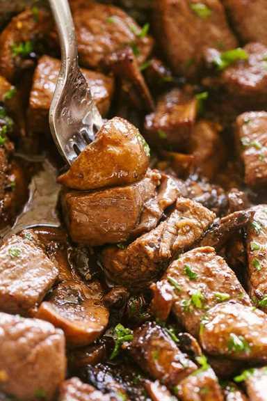 """Setas y trozos de carne en un tenedor. """"Width ="""" 640 """"height ="""" 960 """"data-pin-description ="""" Bocaditos de filete de mantequilla de ajo con champiñones - Bocaditos de filete jugoso con champiñones caramelizados sabrosos cocinados en una deliciosa salsa de mantequilla de ajo. ¡Una receta de una sartén que es TAN simple de hacer y está lista en menos de 20 minutos! # picaduras de filete # ajo # mantequilla # recetas fáciles # steakdinner"""