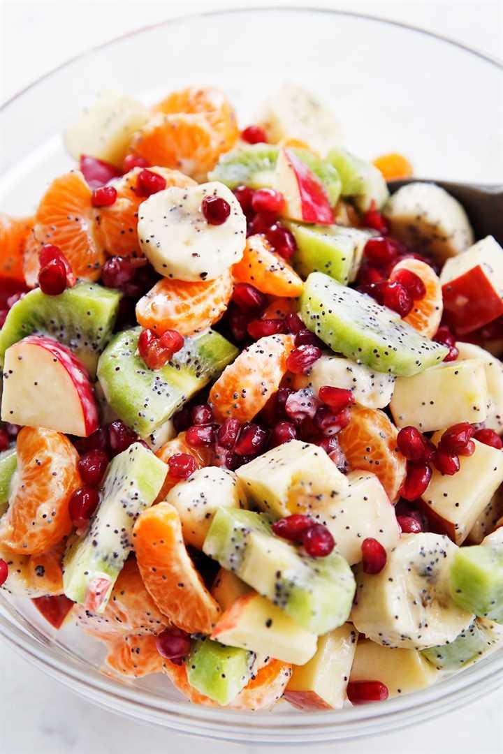 Un plato de ensalada de frutas de invierno con fruta de invierno y aderezo de yogur griego.