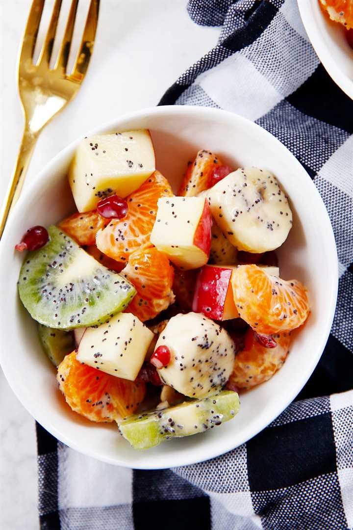 Un tazón de ensalada de frutas de invierno con semillas de amapola y yogur griego.