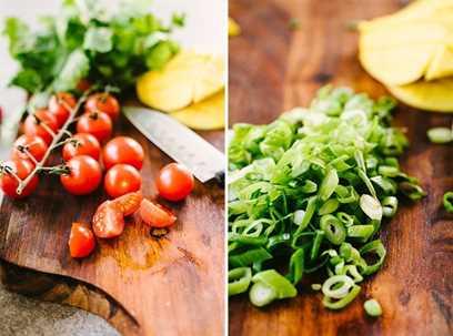 Preparar verduras para una receta de salsa de verano. Tomates cherry cortados a la izquierda; derecha - cebolla verde en rodajas finas sobre una tabla para cortar.