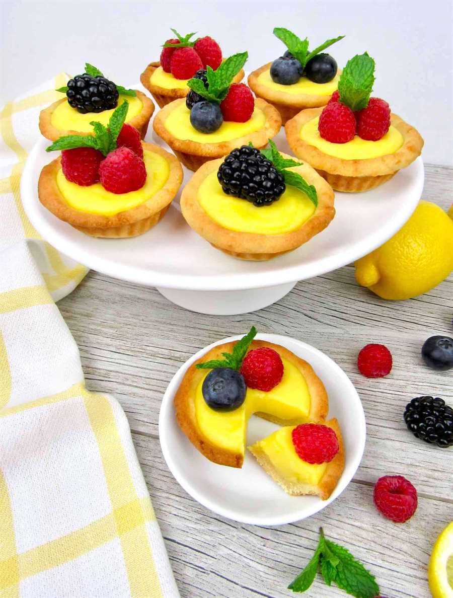soporte de pastel con mini tartas de cuajada de limón con bayas en la parte superior