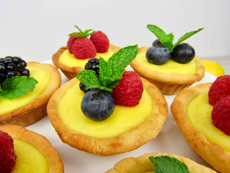 Primer plano de mini tartas de cuajada de limón con bayas en la parte superior