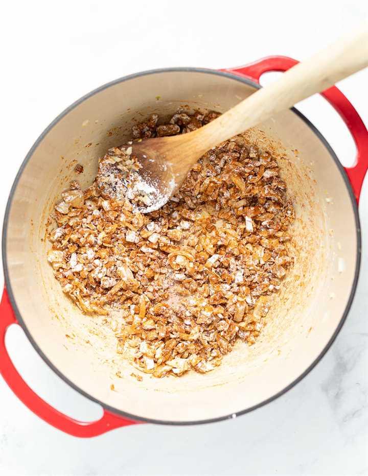 cebollas, ajo, especias y maicena cocinando en una sartén