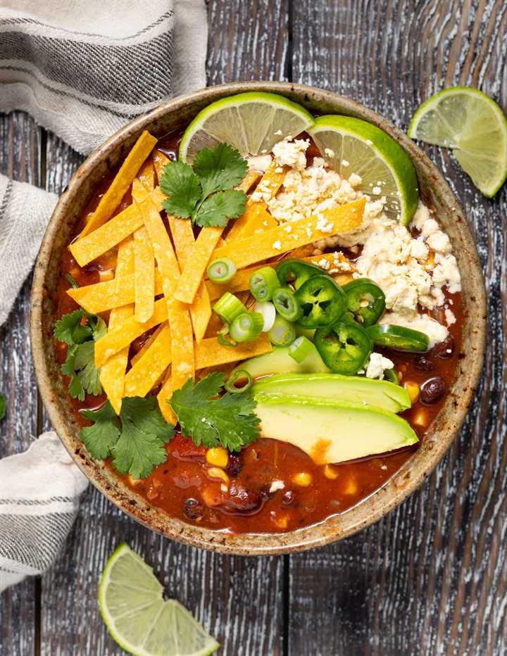 Un tazón de sopa de tortilla vegana pesada sobre un fondo de madera con unas rodajas de limón