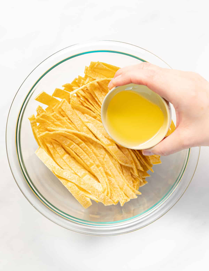 se vierte aceite sobre tiras de tortilla en un tazón