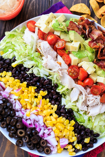 Ensalada Tex-Mex Cobb con frijoles negros, maíz, aguacate, tocino, pollo y chips de maíz frito